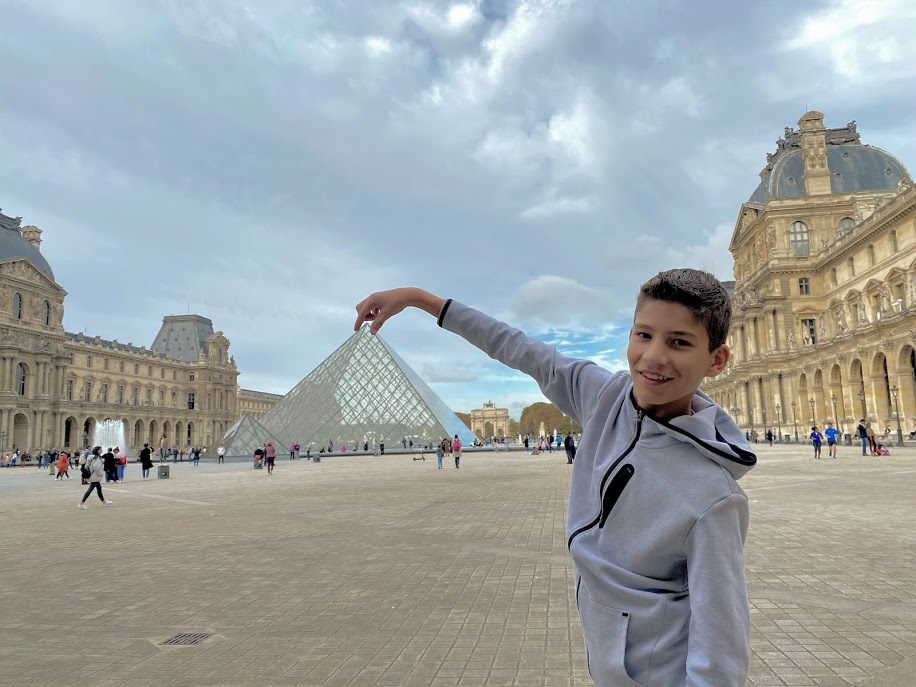 Boy in Louvre forced perspective with pyramid