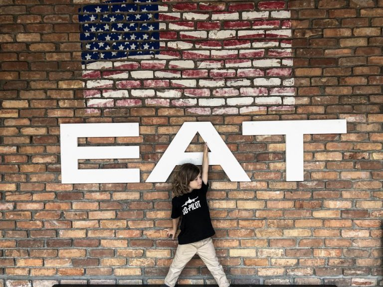 Boy in front of EAT sign