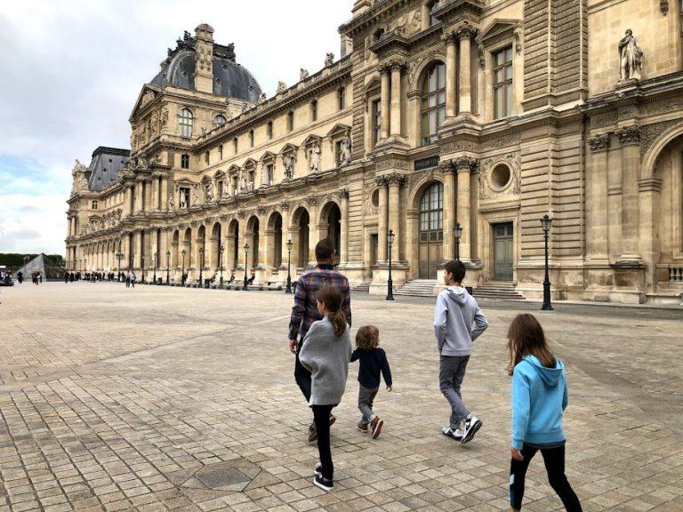 Family walking through Louvre courtyard
